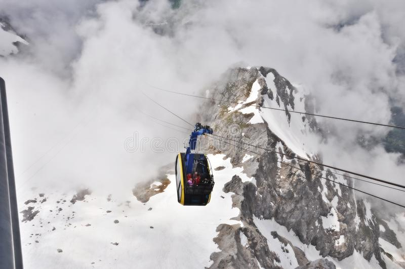 Cable car ride above clouds. The cable ride is over 3000 meters from ground. Sometimes the clouds are below the mountain summit. The location is Dachstein stock photography