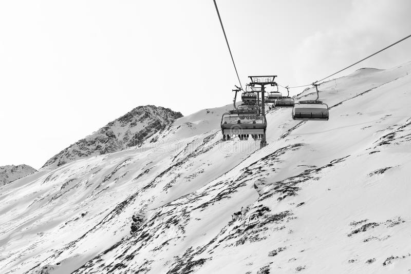 Cable car at a ski resort. Chairlift with skiers. Mountains covered with snow royalty free stock image