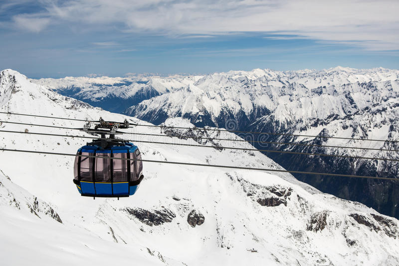 Cable car with ski slope in mountains near stock images