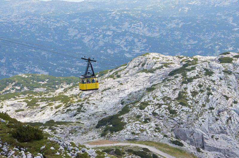 Cable Car to Mountain Dachstein in Salzkammergut region. Austria. Neutral colors. Gray mountains in the background. And people inside stock image