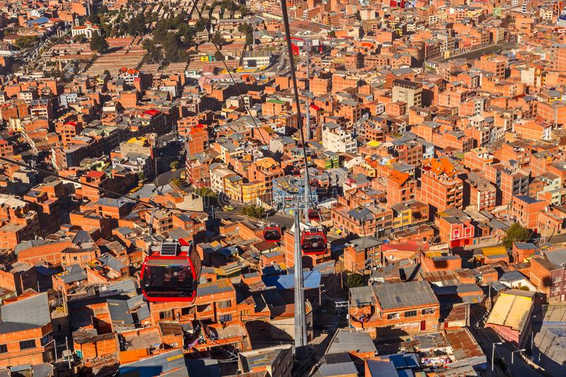 Cable cars or funicular system over orange roofs and buildings of the Bolivian capital, La Paz, Bolivia. Aerial america beauty cableway cart city cityscape royalty free stock images