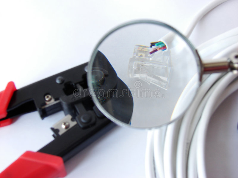Cable crimper&cables. Cable, cat5 & cable crimper under a magnifier royalty free stock images