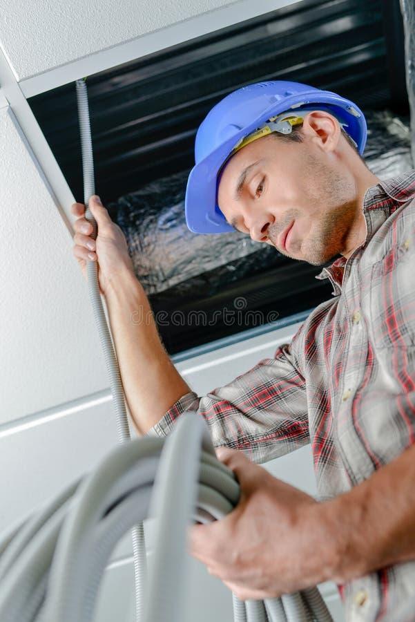 Cable de alimentación del hombre sobre techo suspendido fotos de archivo