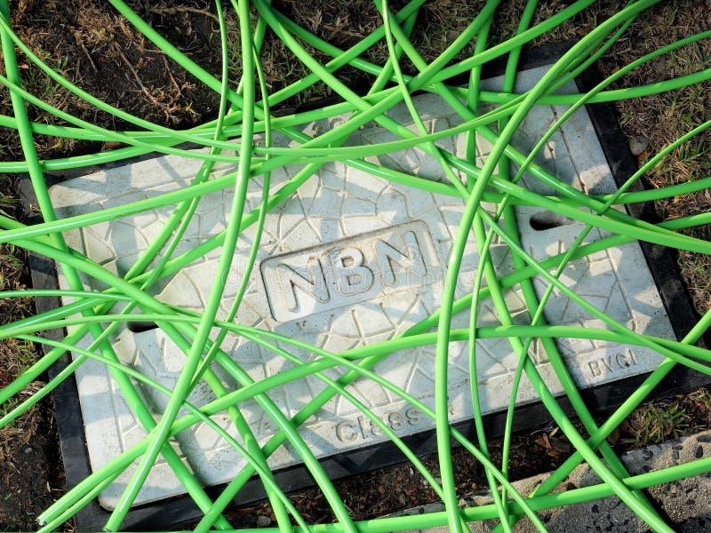 Cable fibroóptico verde de NBN en un lío no estructurado sobre un hoyo con una cubierta concreta del agujero del hombre que exhib foto de archivo