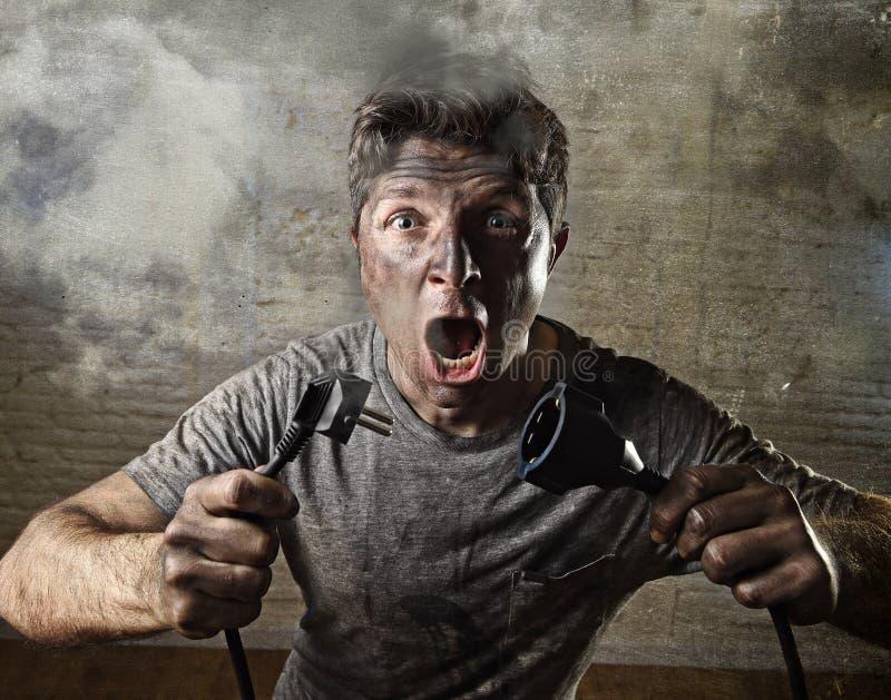 Cable inexperimentado del hombre que sufre accidente eléctrico con la cara quemada sucia en la expresión divertida del choque imagen de archivo