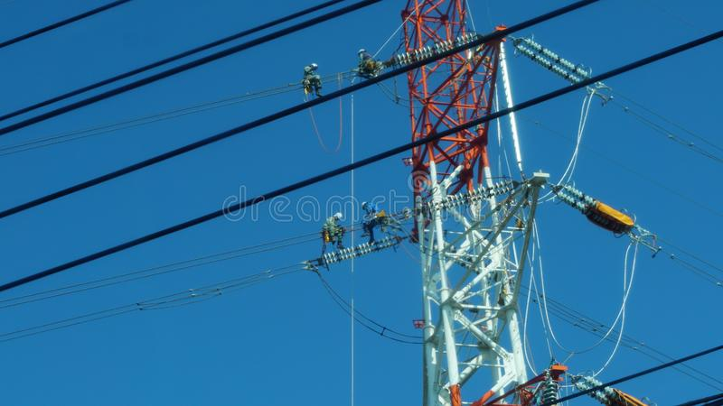 4 cable maintenance technicians sitting on the cables, Fukuoka. Bravery is necessary to do this job. They climbed up to the power tower and worked in pairs. This royalty free stock photography