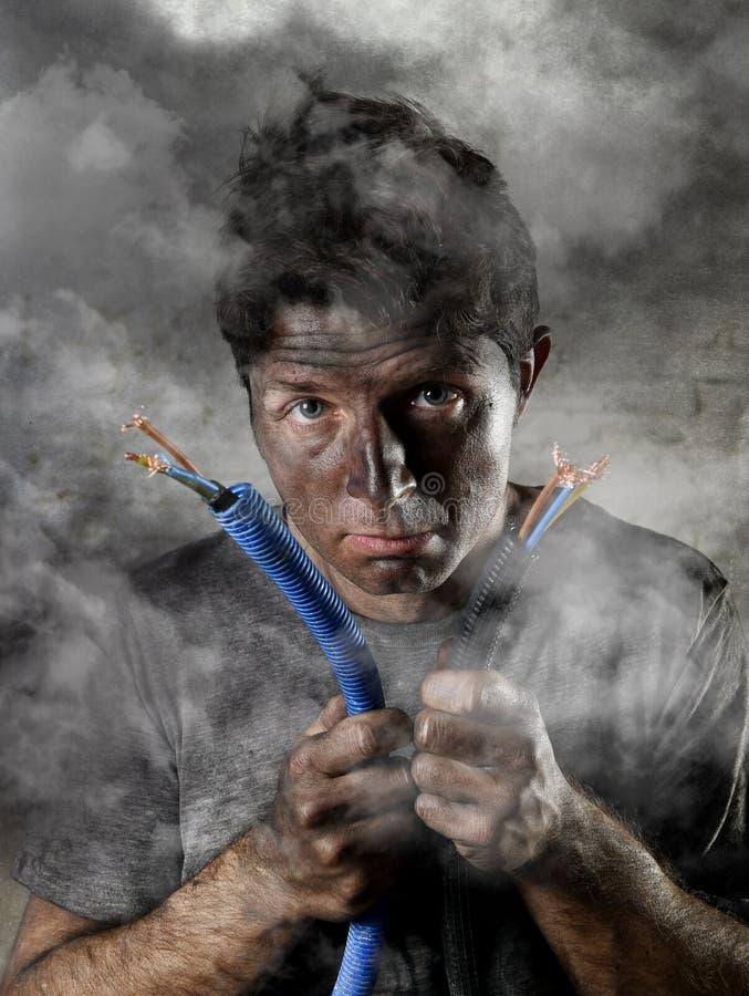 Cable que se une a del hombre inexperimentado que sufre accidente eléctrico con la cara quemada sucia en la expresión divertida d foto de archivo