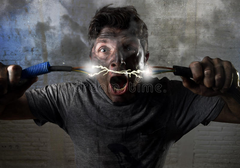 Cable que se une a del hombre inexperimentado que sufre accidente eléctrico con la expresión quemada sucia del choque de la cara imagen de archivo libre de regalías