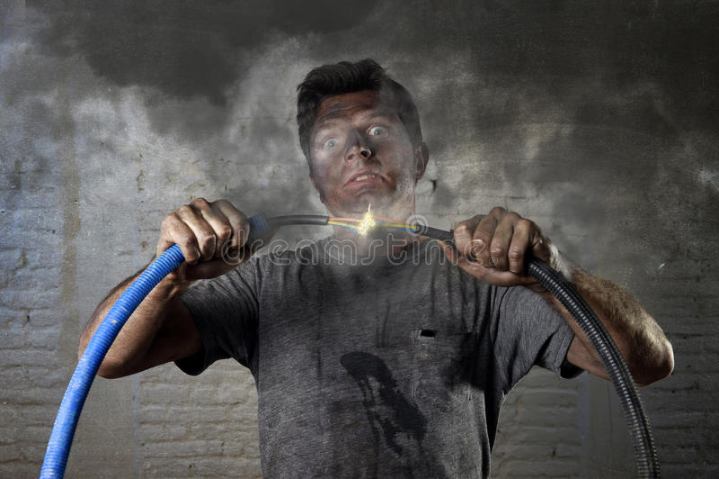 Cable que se une a del hombre inexperimentado que sufre accidente eléctrico con la expresión quemada sucia del choque de la cara fotos de archivo libres de regalías