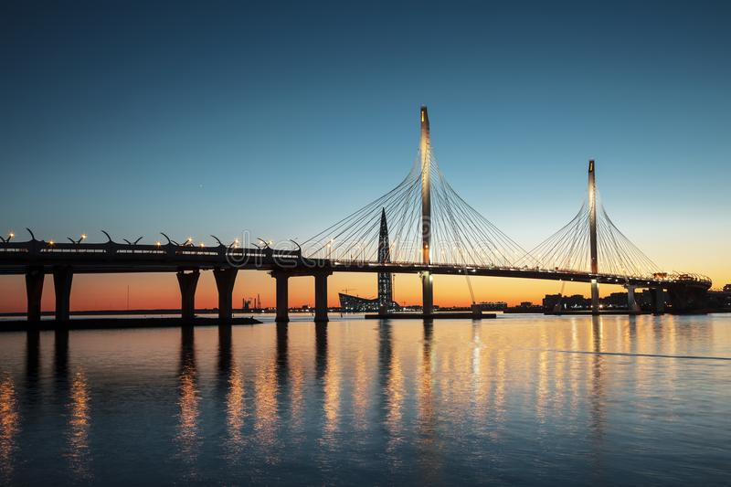The cable-stayed bridge over Petrovsky fairway and the tower of Lakhta center, at sunset, Saint-Petersburg, stock photos