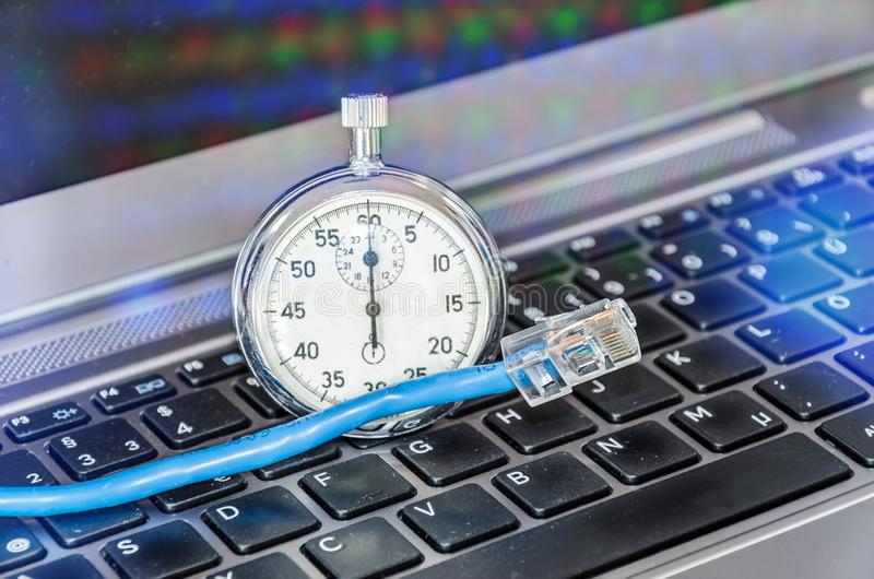 Cable and stopwatch on computer keyboard symbolizing bandwidth of internet connection. Cable and stopwatch on a computer keyboard symbolizing bandwidth of royalty free stock photography
