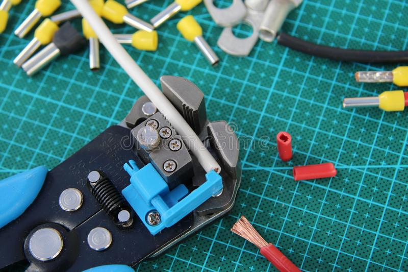 Cable Stripping with Stripping tool. The grey cable is clamped in the cable Stripping tool. Near lie the pieces red cable stripped. On the back crimp terminals stock photo
