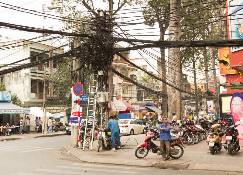 Cable tangle in Saigon Vietnam. Bundles of cables line the streets of Ho Chi Minh City in Vietnam. To see a ladder and repairman is not uncommon. Vietnam has royalty free stock image