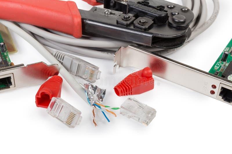 Cable y conectores del par trenzado contra los componentes de la red, herramienta que prensa imagenes de archivo