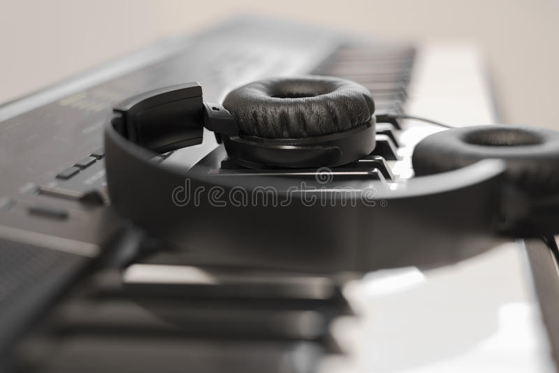 Cabled headset over electronic piano keyboard. Black generic over the ears headset resting on piano keys royalty free stock image