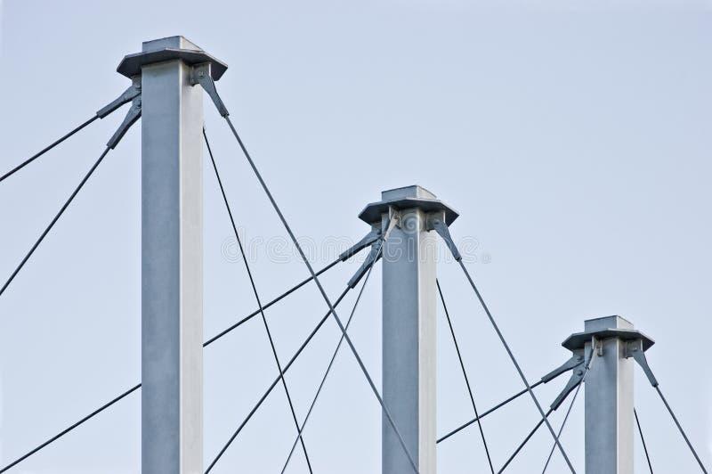 Cables atados del tejado de la suspensión, tres Grey Masts alto, anclas Swooping Cable-suspendidas del pilón del tejado, Pale Blu imagen de archivo