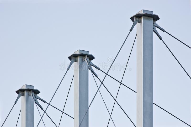Cables atados del tejado de la suspensión, tres Grey Masts alto, anclas Swooping Cable-suspendidas del pilón del tejado, Pale Blu foto de archivo