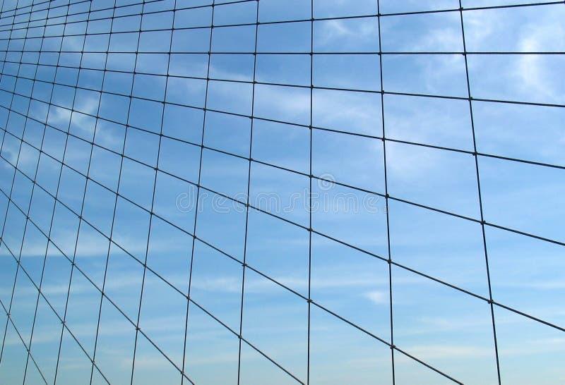 Cables del puente de Brooklyn contra el cielo con las nubes Wispy imagenes de archivo