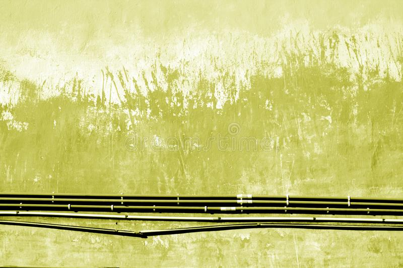 Cables on old grungy cement wall in yellow tone. royalty free stock photos