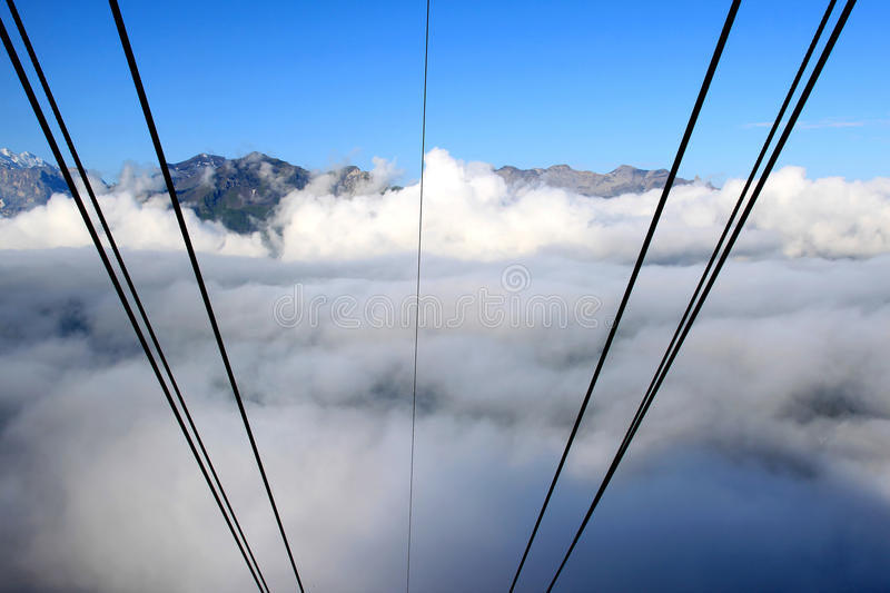 Cables from a Swiss cablecar disappear into clouds. View from the top station of the cableway on the Mannlichen upon the descending cables disappearing into the stock photo