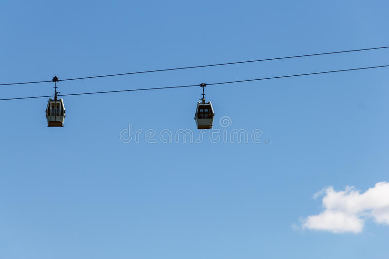 Cableway cabins on the background of the blue sky stock photos