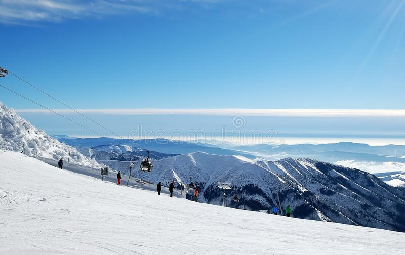Cableway, skiers and mountains peaks of Low Tatras  in the ski resort  Jasna, Slovakia royalty free stock photography