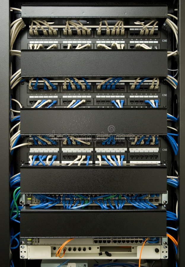 Cabling Rack. Patch cables plugged in to ethernet swicth and patch panel, in managed cabling rack