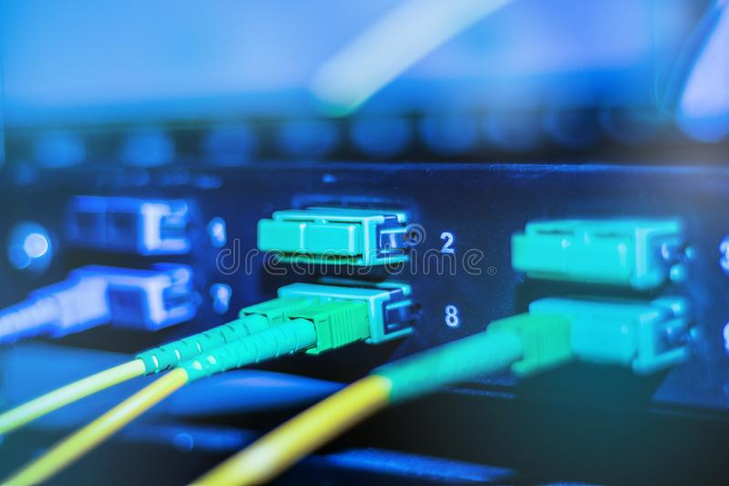 Cabo ótico em dispositivos do Internet Cabo de fibra ótica verde e amarelo no interruptor imagens de stock royalty free