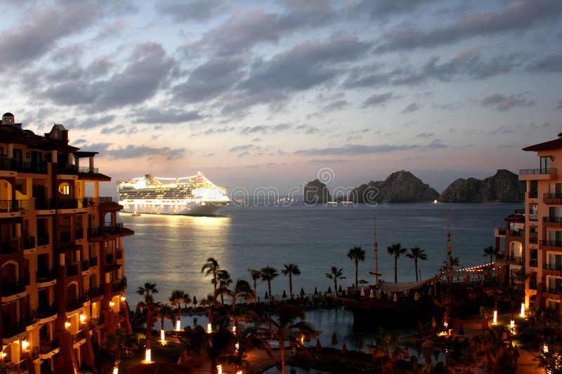 Cabo at Dawn. The sun coming up at a luxury resort in Cabo, Mexico, with a large cruise ship dropping anchor stock photo