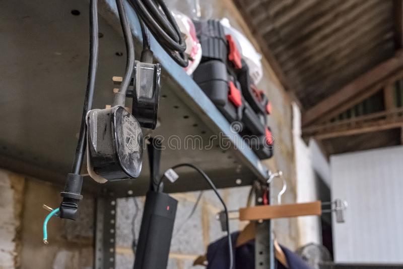 Cabo de alimentação bonde, alguns com tomadas BRITÂNICAS o shelving de suspensão visto do metal em uma oficina foto de stock royalty free