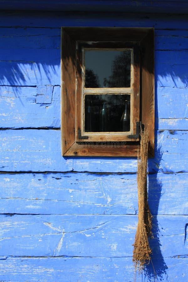 Cabo de vassoura em uma janela em uma parede de madeira azul foto de stock