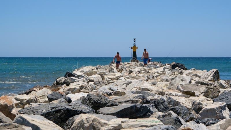 CABO PINO, ANDALUCIA/SPAIN - 2 ΙΟΥΛΊΟΥ: Άνθρωποι που εξερευνούν τους βράχους στοκ εικόνα