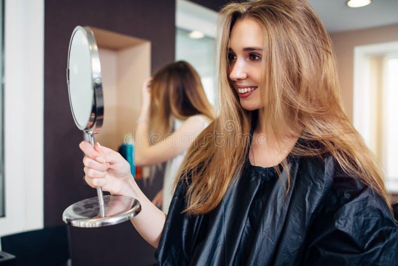 Cabo que lleva del cliente femenino joven que sostiene un espejo del maquillaje que mira y que sonríe en el salón de belleza sati fotografía de archivo