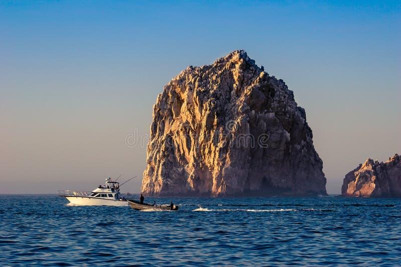 Cabo San Lucas/Мексика - 13-ое августа 2007: Взгляд на плавании рыбацкой лодки рядом с большим утесом стоковое изображение