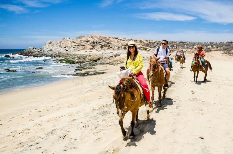 Tourists horseback riding on the beach in Cabo San Lucas, Baja California. Cabo San Lucas, Mexico - 2019. Tourists horseback riding on the beach in Cabo San stock images