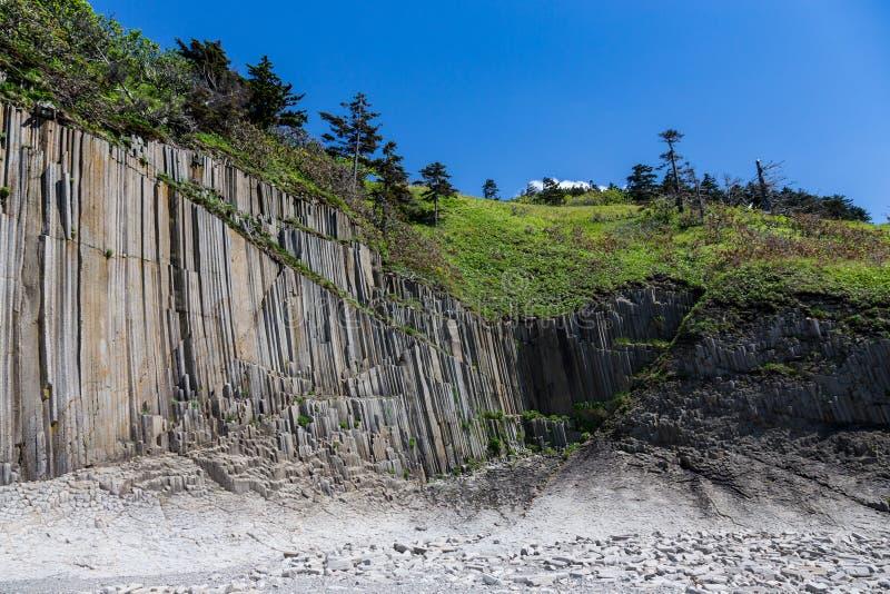 Cabo Stolbchaty Cabo na costa oeste da ilha de Kunashi fotos de stock royalty free