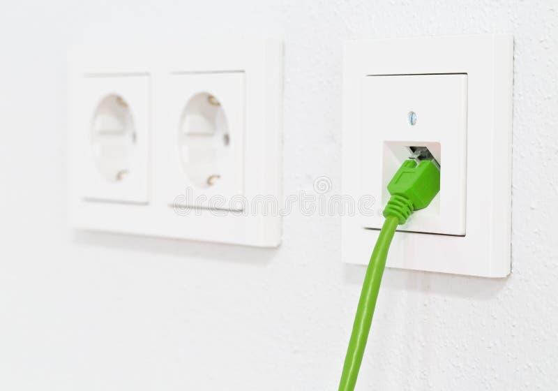 Cabo verde da rede na tomada de parede para a conexão dos ethernet do lan do escritório ou da propriedade privada com a opinião l imagens de stock royalty free