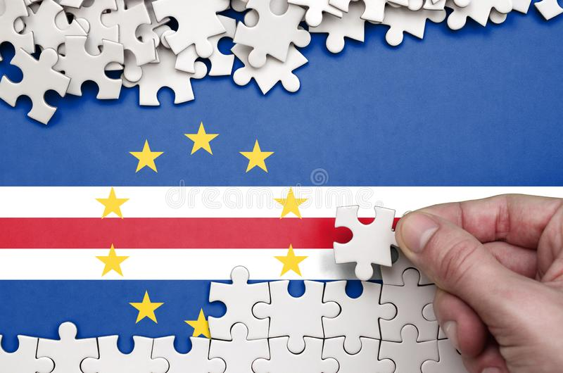 Cabo verde flag is depicted on a table on which the human hand folds a puzzle of white color stock image