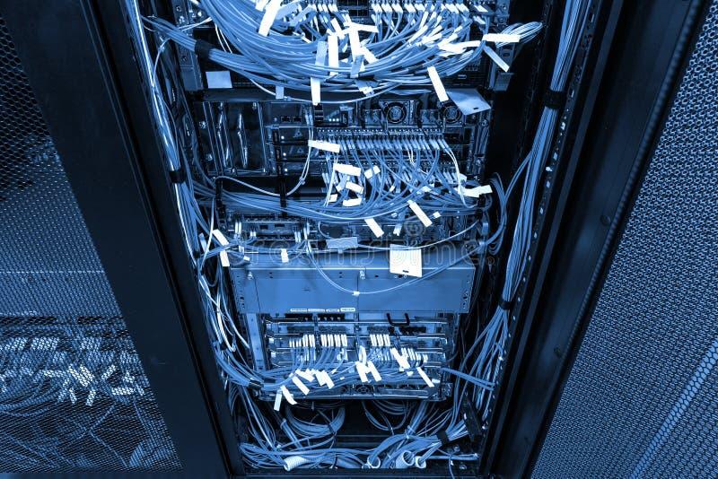 Cabos de LAN de UTP do cubo e do remendo da rede no armário da cremalheira com tonificação azul fria escura imagem de stock