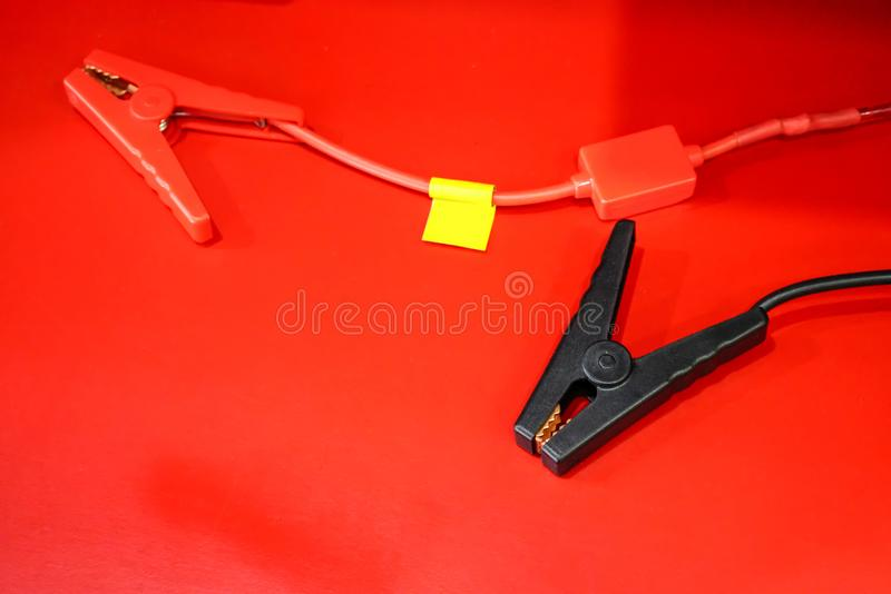 Cabos de ligação em ponte vermelhos e pretos isolados no vermelho foto de stock royalty free