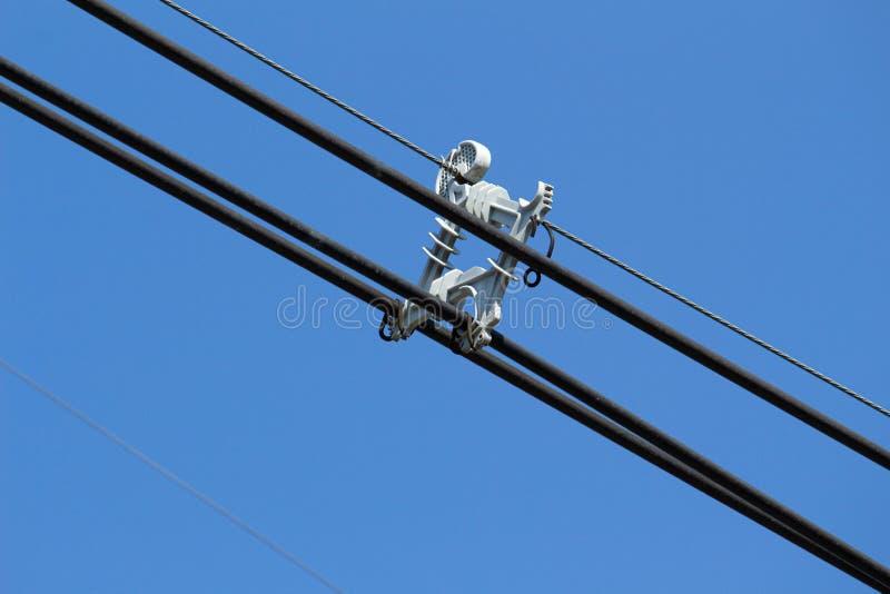 Cabos elétricos com amortecedor espaçador sobre fundo azul imagem de stock royalty free