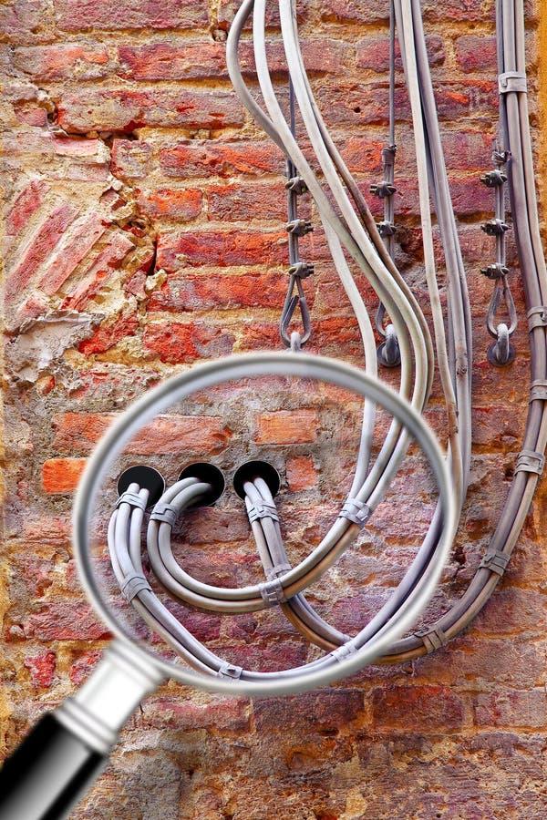 Cabos elétricos externos da linha elétrica e de telefone fixados a uma parede de tijolo velha para a distribuição do fornecimento foto de stock