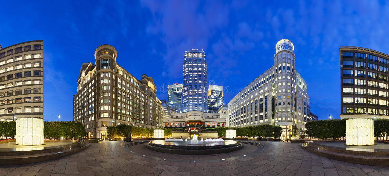 Cabot Square In London at night. Cabot Square panorama in the modern Canary Wharf quarter with its banks and skyscrapers at night royalty free stock photo