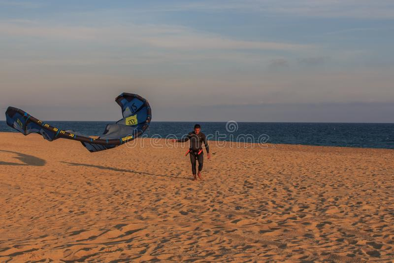 Cabrera de Mar,Barcelona/Spain; 02 08 2019: A good afternoon to practice Windsurfing and Kitesurfing Flysurf at Cabrera beach at. Sunset with the waves of the stock photography