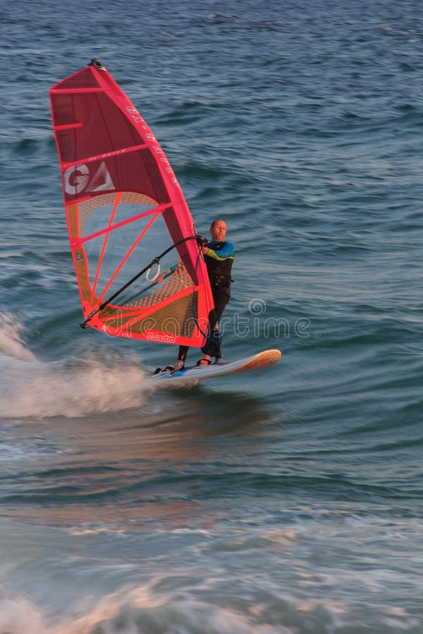 Cabrera de Mar,Barcelona/Spain; 02 08 2019: A good afternoon to practice Windsurfing and Kitesurfing Flysurf at Cabrera beach at. Sunset with the waves of the royalty free stock image