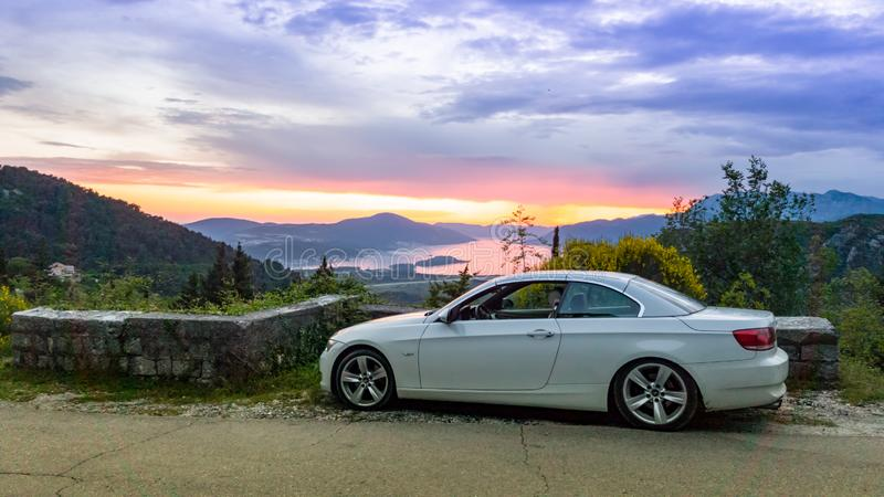 Cabriolet convertible roadster parked on the street with sunset in the background. Luxury white convertible on the background of the sunset sky in the mountains stock images