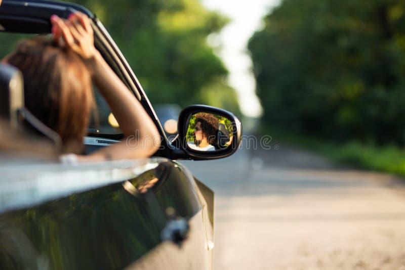 Cabriolet noir sur la route un jour ensoleillé Dans le miroir latéral est la réflexion du jeune homme aux cheveux foncés avec la  photo stock