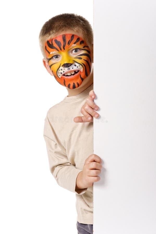 Cabrito con la cara pintada tigre. En el fondo blanco foto de archivo