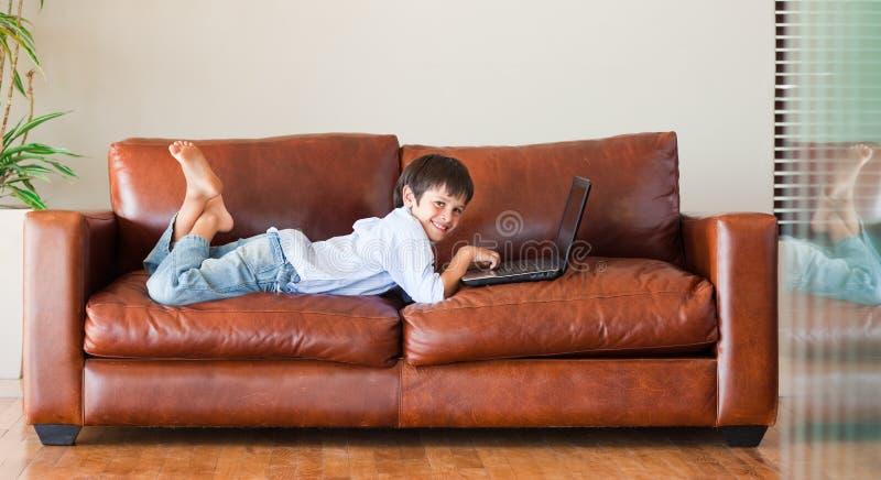 Cabrito con una computadora portátil en el sofá foto de archivo
