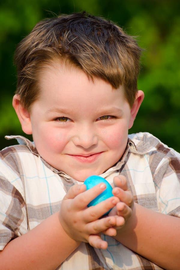 Cabrito del muchacho del niño que sostiene el huevo de Pascua colorido imagenes de archivo